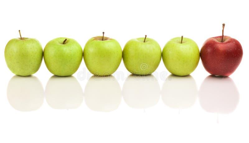 Manzanas verdes con el arranque de cinta rojo imagenes de archivo