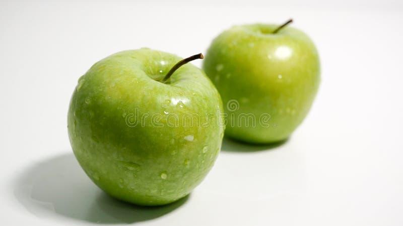 Manzanas verdes con las gotitas de agua en el fondo blanco foto de archivo