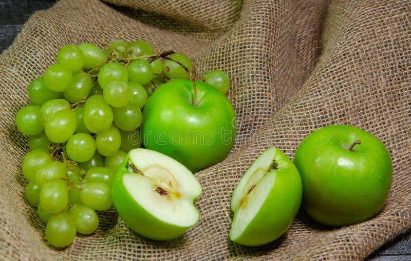 Manzanas verdes de la uva en una caja fotos de archivo