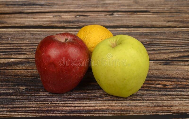 Manzanas verdes y rojas maduras en un fondo de madera de la tabla fotografía de archivo