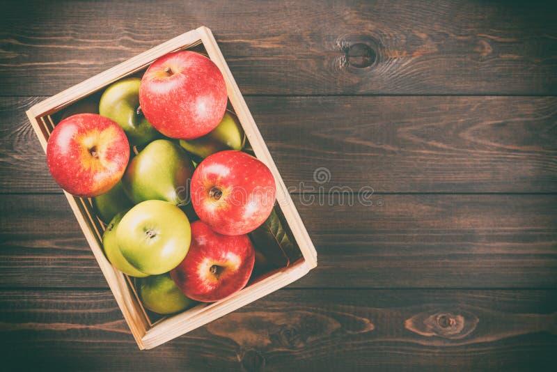 Manzanas verdes y rojas maduras en una caja de madera en fondo rústico de madera marrón oscuro Imagen estacional del otoño con la imagen de archivo