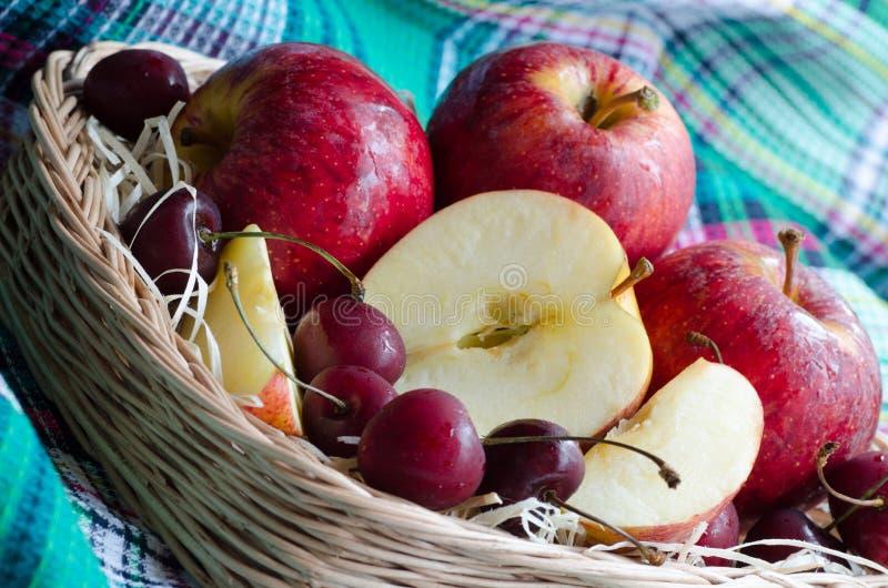 Manzanas y cereza rojas en una toalla imagen de archivo