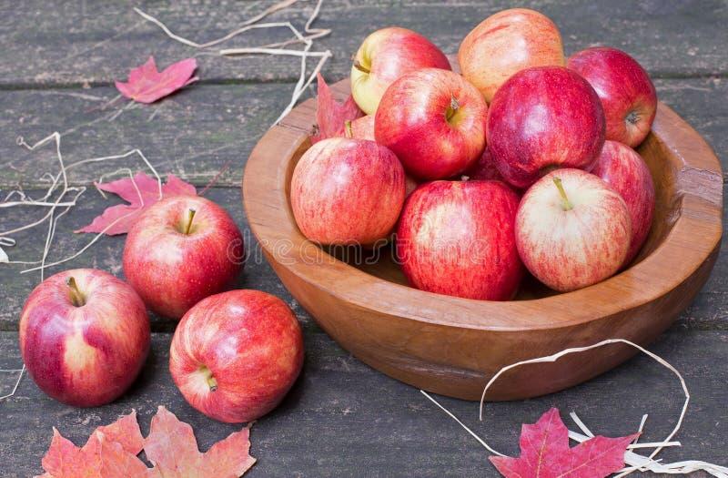 Manzanas y cuenco rojos en fondo de madera rústico fotos de archivo libres de regalías