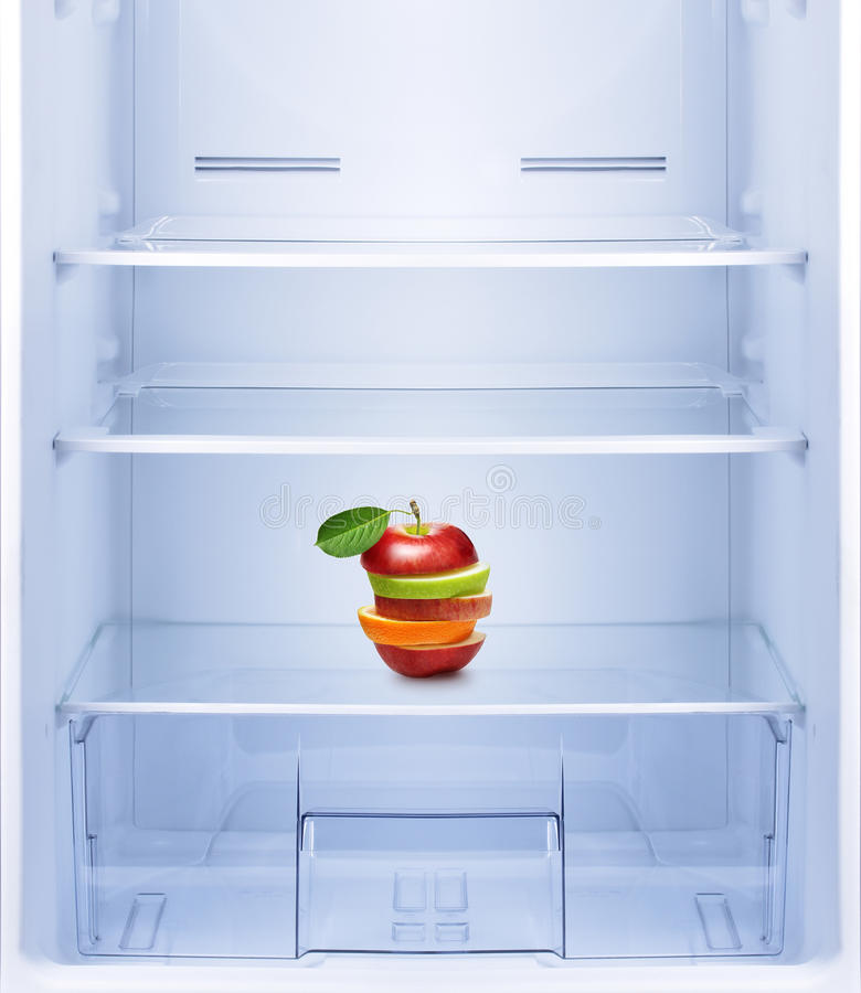 Manzanas y fruta anaranjada en refrigerador vacío foto de archivo