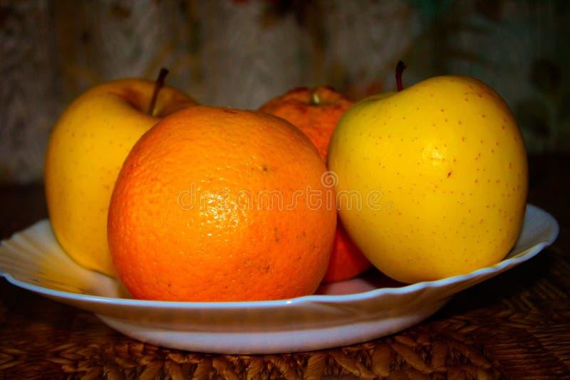 Manzanas y naranjas maduras frescas en un disco imagenes de archivo