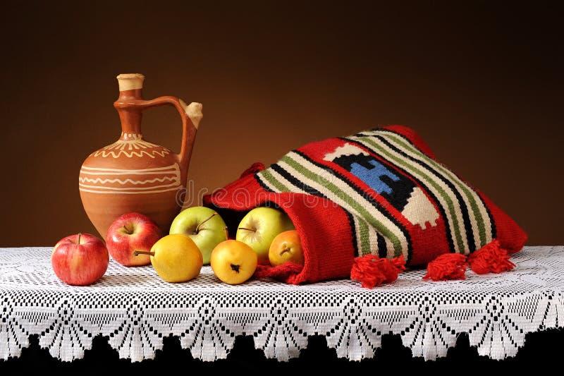 Manzanas y peras frescas en bolso étnico imagenes de archivo