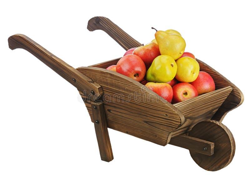 Manzanas y peras rojas en la carretilla de mano de madera aislada en el backgr blanco imagen de archivo libre de regalías