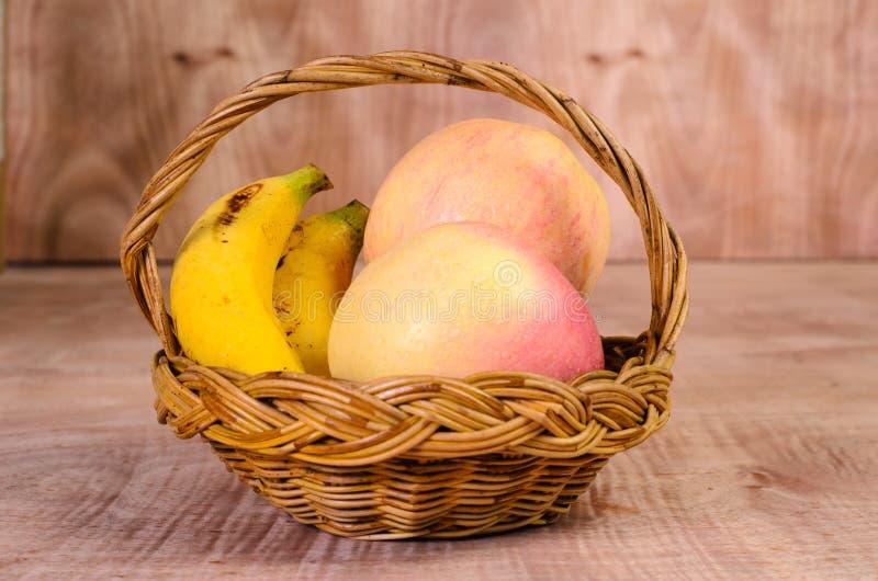 Manzanas y plátanos en cesta en la madera foto de archivo