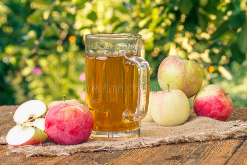 Manzanas y sidra de manzana escogidas en el cubilete de cristal en los tableros de madera fotos de archivo libres de regalías