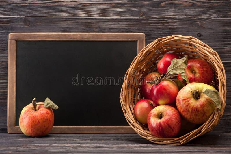 Manzanas y tablero de tiza rojos maduros fotos de archivo