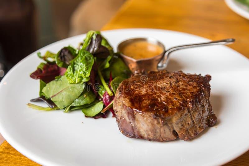 Manzo, bistecca arrostita con insalata sul piatto bianco fotografia stock libera da diritti