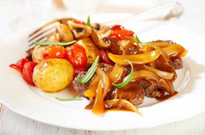 Manzo brasato con la salsa della cipolla e le verdure al forno del forno immagine stock