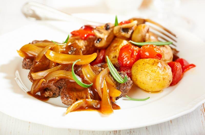 Manzo brasato con la salsa della cipolla e le verdure al forno del forno immagini stock