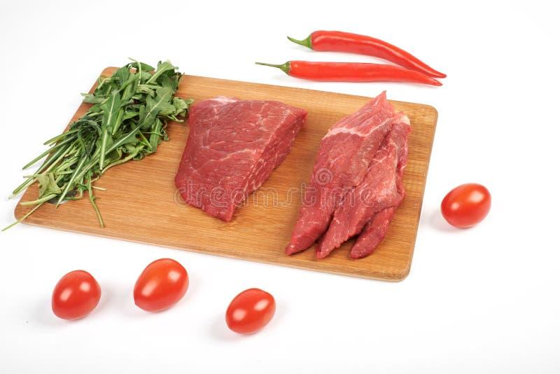 Manzo crudo affettato sul tagliere e verdure isolate su fondo bianco immagine stock libera da diritti