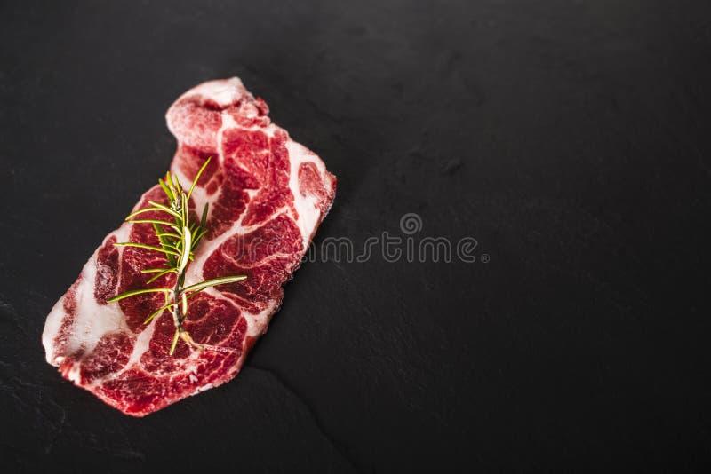Manzo della lonza di maiale pronto a grigliare sopra un piatto della pietra del nero scuro, stu immagini stock libere da diritti