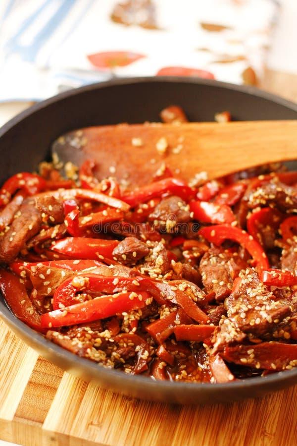 Manzo sauteed con il peperoncino rosso rosso in pentola nera fotografia stock