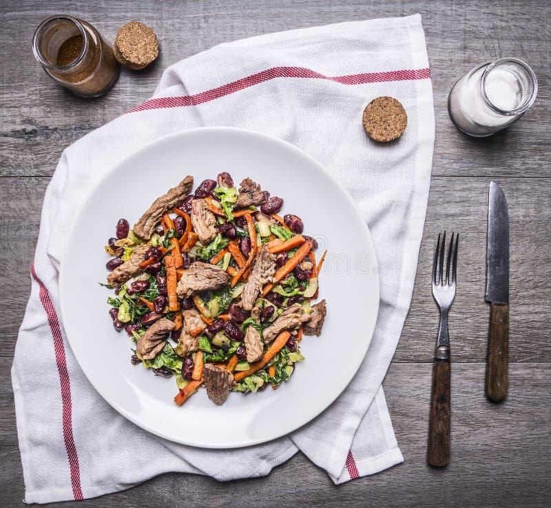 Manzo sauteed con le verdure arrostite sul piatto bianco con il coltello e la forcella su un tovagliolo con le spezie sul princip immagine stock libera da diritti