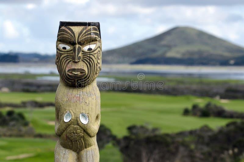 Maori carving. Against Rangiputa mountain in Karikari peninsula, New Zealand royalty free stock image