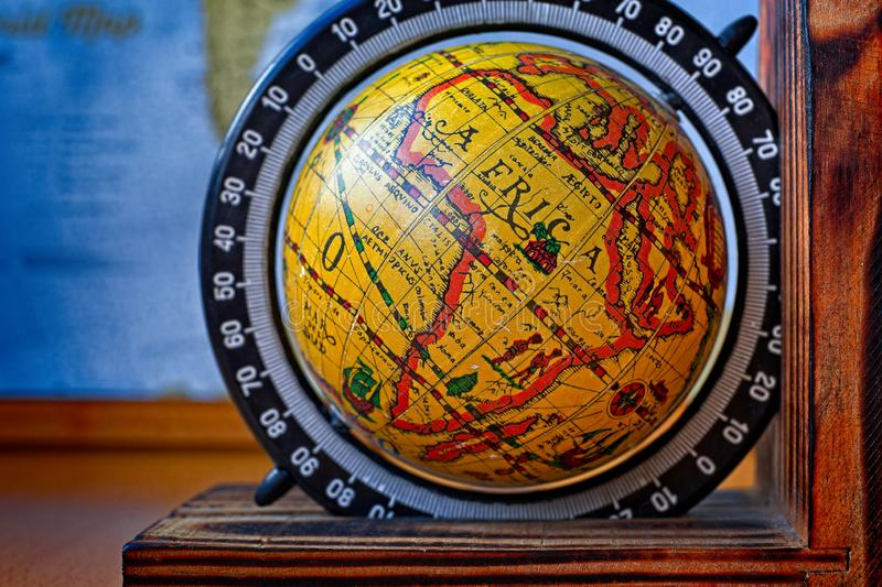 Map of Africa on an ancient globe with world map in the background stock images