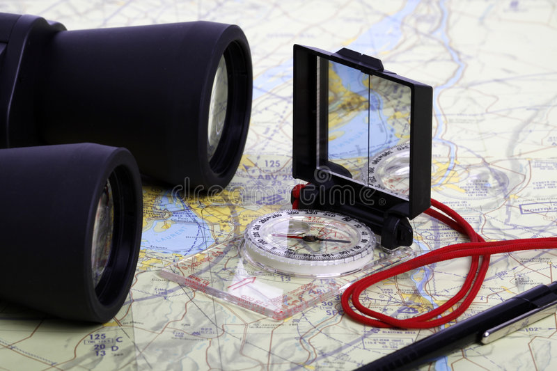Map, Binoculars and compas -1. Binoculars, compass and a pen on a map. Kit for the adventurer. Concept for treasure hunt stock photography