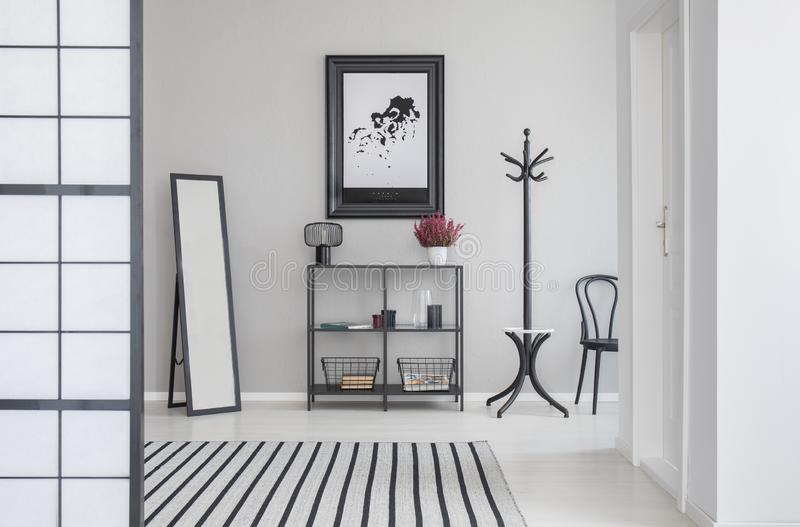 Map in black frame on the grey wall of corridor with mirror, shelf, hanger and hair royalty free stock photo