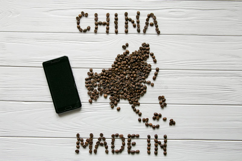 Map of the China made of roasted coffee beans laying on white wooden textured background with phone. Made in China. Space for text stock images
