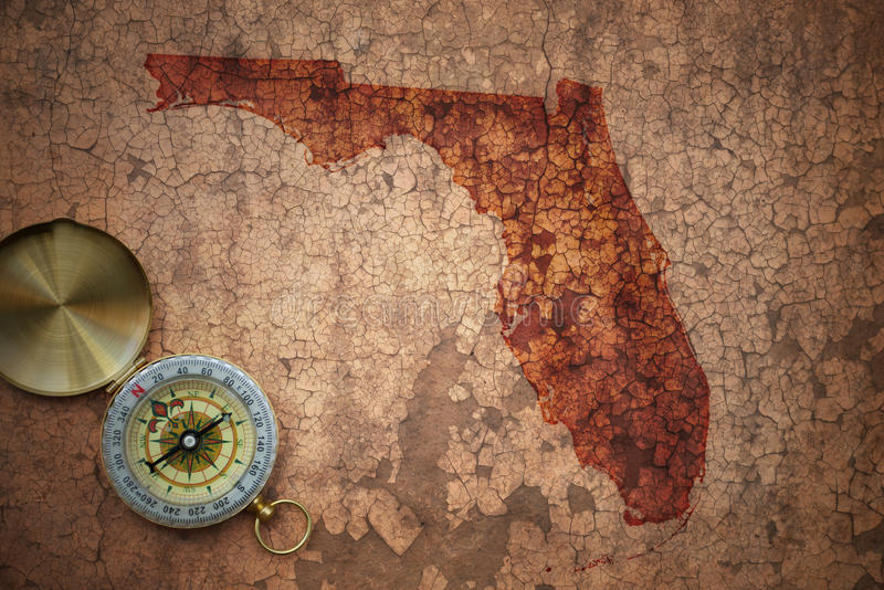Map of florida state on a old vintage crack paper. Background with compass stock photography