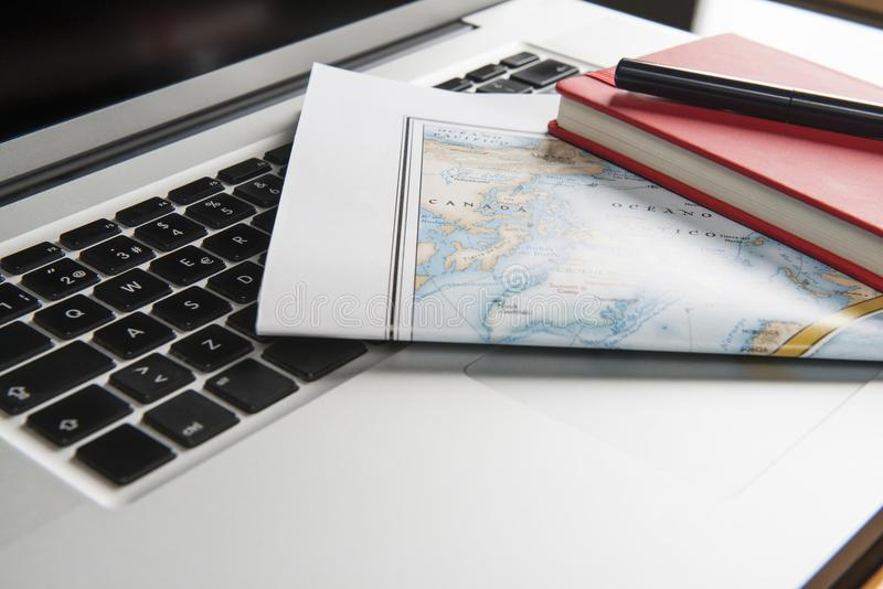 Map, notebook and ball-point pen on laptop. Color photograph of a laptop on which there is a map, a notebook and a pen stock images