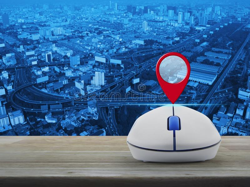 Map pointer navigation concept. Map pin location button with wireless computer mouse on wooden table over city tower, street and expressway, Map pointer royalty free stock photography