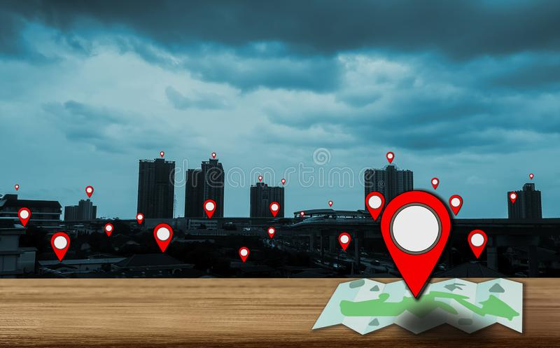 Map pointer icon placed on a wooden table, background is a view of the city and skyscrapers at sunset, With the concept of using royalty free stock photo