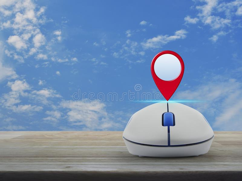 Map pointer navigation concept. Map pin location button with wireless computer mouse on wooden table over blue sky with white clouds, Map pointer navigation stock images
