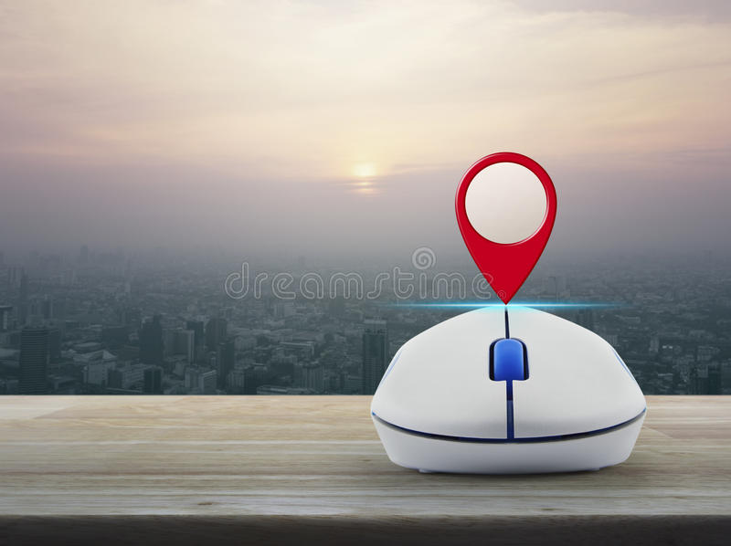 Map pointer navigation concept. Map pin location button with wireless computer mouse on wooden table over modern city tower at sunset, vintage style, Map pointer royalty free stock images