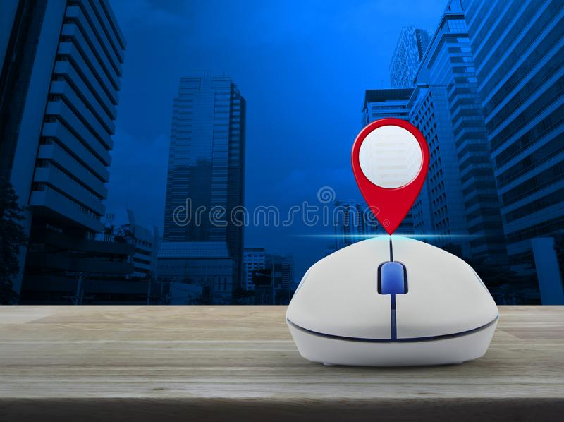 Map pointer navigation concept. Map pin location button with wireless computer mouse on wooden table over modern office city tower, Map pointer navigation stock photo