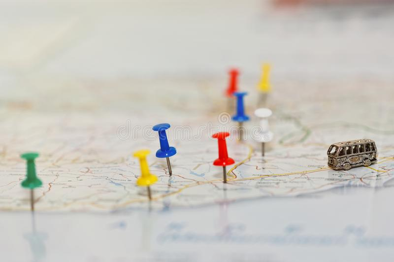 Vacation travel by coach concept. Map with road network and with pushpins marking country highlights and tourist attractions and a tiny toy coach on the road royalty free stock image