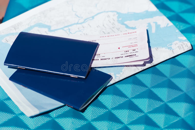 Map, two passports and tickets lying on blue baggage stock photo