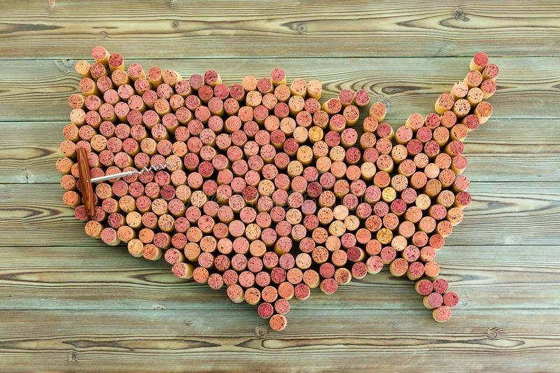 Map of the United States formed of used wine corks. Map of the United States formed of used wine bottle corks with a corkscrew overlaid on top over a rustic wood royalty free stock images