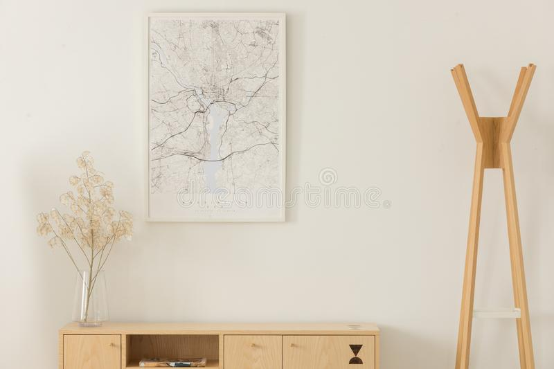 Map in white frame, flower in a glass vase on wooden shelf, next to wooden hanger, real photo. With mockup stock photo