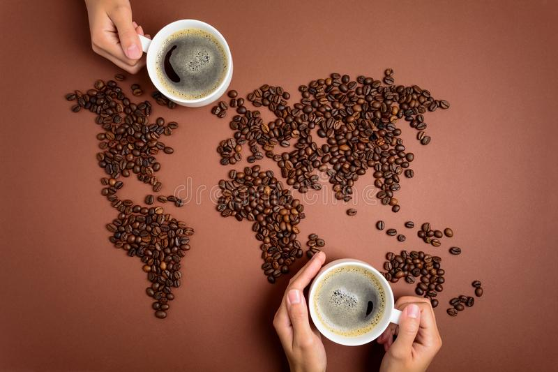 Map of the world made of roasted coffee beans on brown paper background. stock image