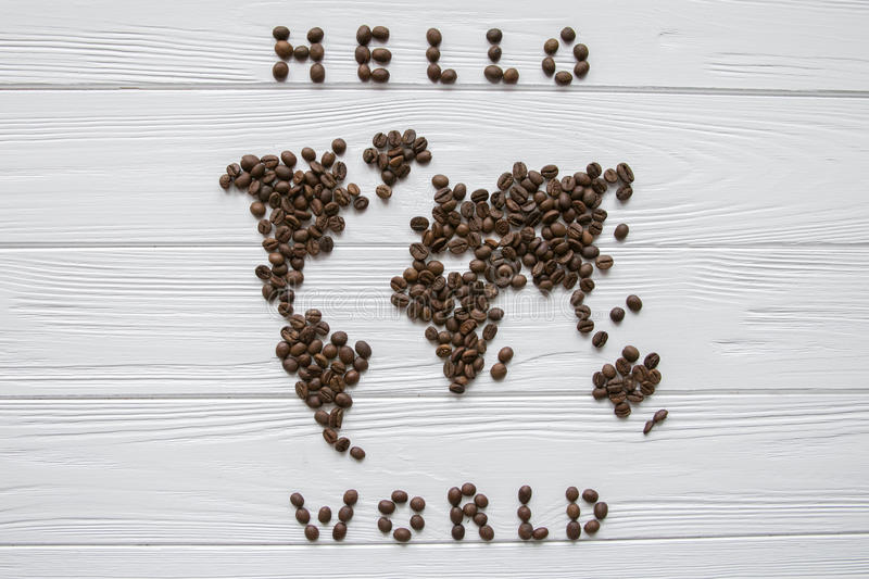Map of the world made of roasted coffee beans laying on white wooden textured background with signature `Hello world`. Space for text stock photography