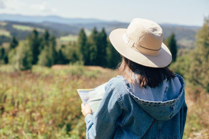 Mapa à moda da terra arrendada da menina do moderno e viagem em montanhas ensolaradas Mulher no mapa de exploração do chapéu e ca fotos de stock
