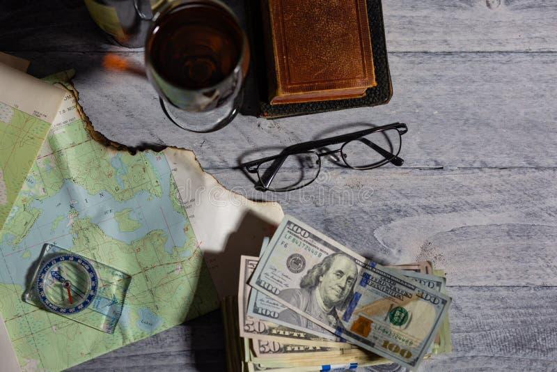 Mapa, bússola, vinho, dinheiro, livros e óculos fotos de stock