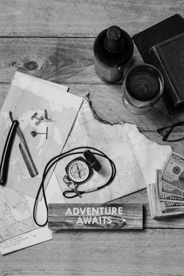 Mapa, bússola, vinho, dinheiro, livros, lâminas, ligações de algemas, tachado e óculos, preto e branco imagens de stock