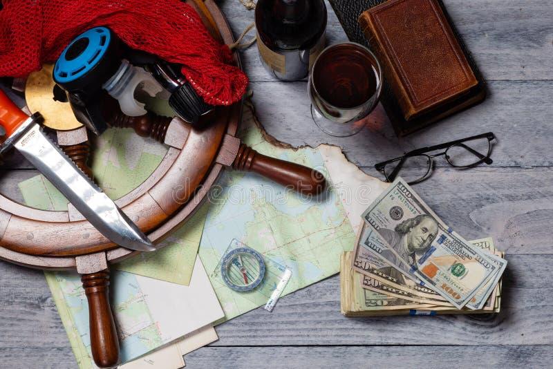 Mapa, bússola, vinho, dinheiro, livros, roda do navio, óculos, faca e equipamento de mergulho fotografia de stock royalty free