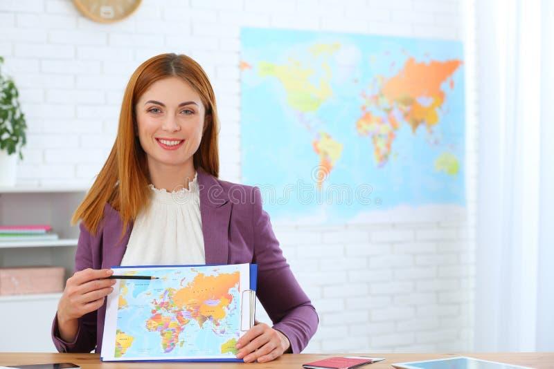 Mapa bonito da exibição do consultante na agência de viagens imagens de stock royalty free