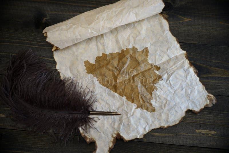 Mapa Bosnia i Herzegovina na roczniku tapetujemy z starym pi?rem na drewnianym tekstury biurku zdjęcia royalty free