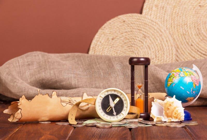 Mapa, compás, globo, reloj de arena y monedas viejos en fondo marrón fotos de archivo libres de regalías