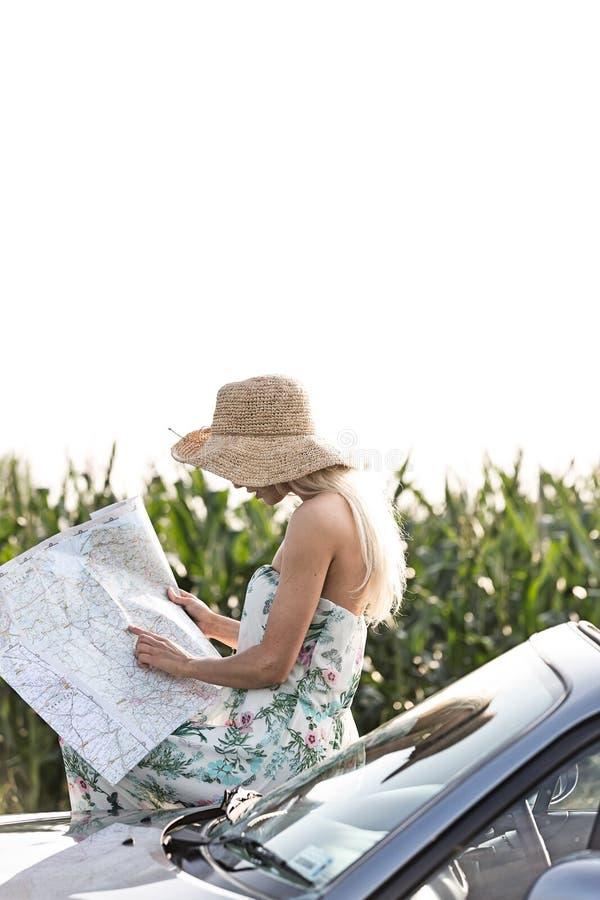 Mapa da leitura da mulher ao inclinar-se no convertible fotografia de stock