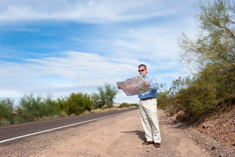 Mapa da leitura do homem na estrada abandonada fotografia de stock