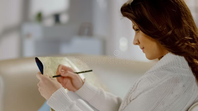 Mapa de exame da jovem mulher bonita, viagem por estrada planejando com as atrações turísticas fotos de stock royalty free
