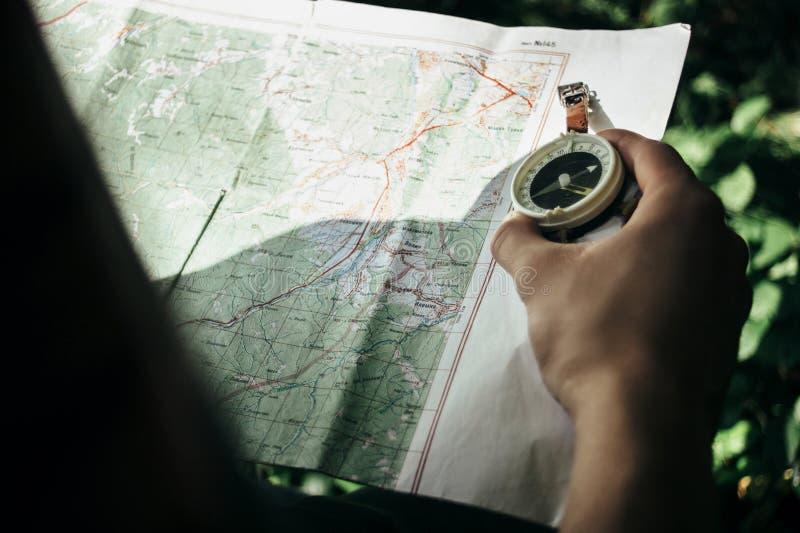 Mapa de exploración del viajero con el compás en bosque soleado en el soporte foto de archivo libre de regalías